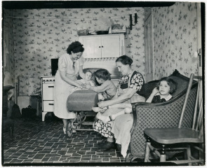 Mrs. Bella Iveson and her family inside their home at 111 Washington Ave