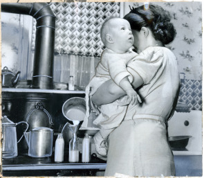 Mrs. Bella Iveson pours formula for baby Rose Marie in kitchen at 111 Washington Ave