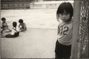 A young Hmong girl stands in a South Philadelphia playground.