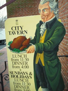 A sign featuring a Colonial waiter at the City Tavern