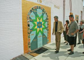 "Artist Joe Brenman and ""Doorways to Peace"" mural. Image provided by City of Philadelphia Department of Records"
